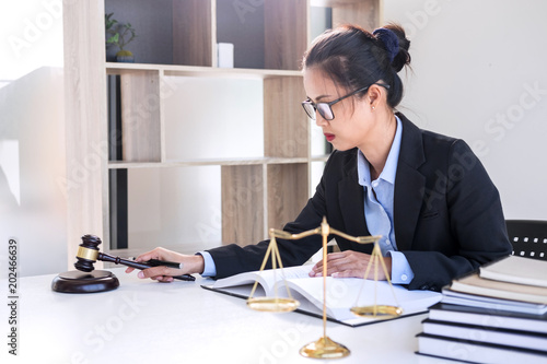 Fényképezés  Judge gavel with scales of justice, professional female lawyers working having at law firm in office