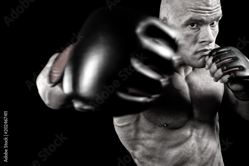 Powerful fighter punching in front of black background
