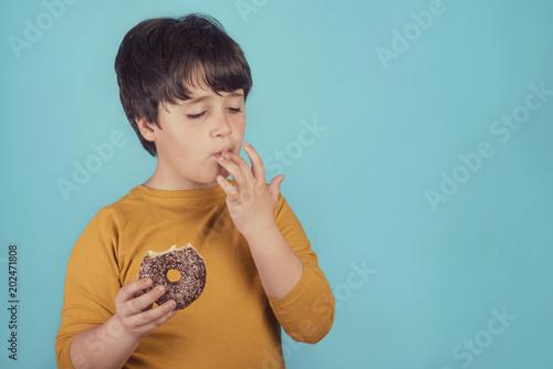 Foto niño comiendo una rosquilla de chocolate sobre fondo azul