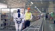 Factory engineer controls a robot, while it works with a tool. 4K.