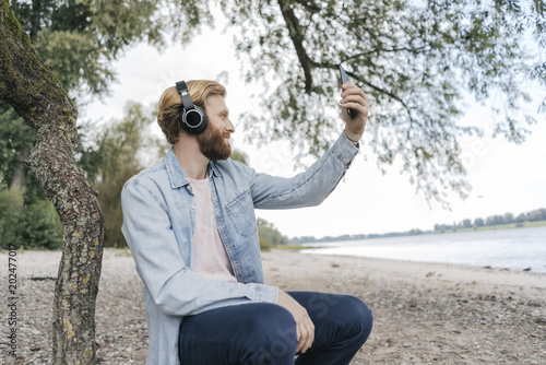 Germany, Duesseldorf, man with  headphones taking selfie on the beach with smartphone