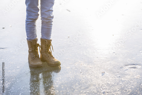 Germany, Brandenburg, Lake Straussee, feet with boots on frozen lake