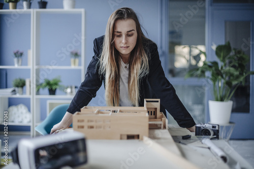 Architect looking at architectural model in office