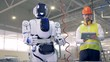 A male worker switches on a robot to start a work.