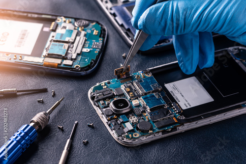 Fotografía  The asian technician repairing the smartphone's motherboard in the lab with copy space