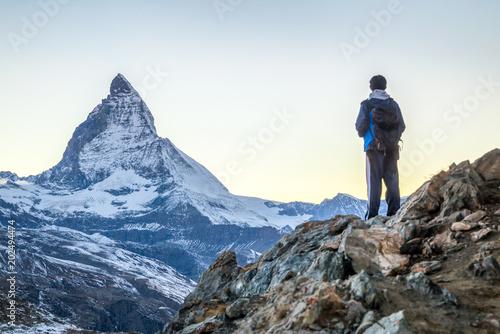 Poster de jardin Alpinisme Junger Mann beim Bergsteigen in den Schweizer Alpen mit Matterhorn im Hintergrund