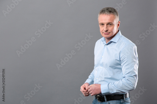 Fototapety, obrazy: Successful entrepreneur. Serious pleasant businessman looking at you while standing against grey background