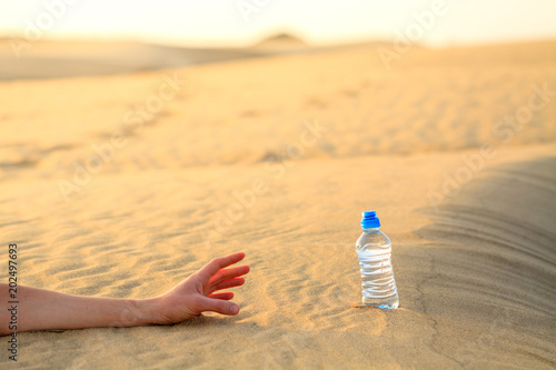 Canvas Print Hand try to catch the bottle of water on sand desert in hot temperature