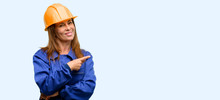Engineer Construction Worker Woman Pointing Away Side With Finger Isolated Blue Background