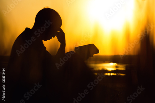 Photo silhouette of a young man with a Bible, male praying to God in nature, the conce