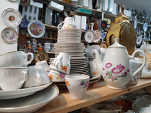 Different Used Vintage Porcelain Dishes And Other Home Related Objects In Flea Market Second Hand Shop
