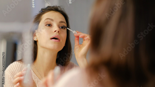 b12535b4f06 beauty makeup tutorial blog. vogue glamour fashion lifestyle. young  beautiful girl applying mascara to eyelashes in front of the mirror