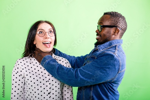 African man jokingly strangles a girl with a protruding tongue on a green backgr Tablou Canvas