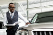 African man with glasses inspects a new car in the showroom