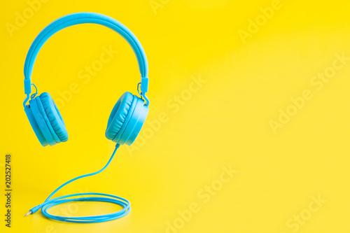Photo  Bright blue headphones on yellow
