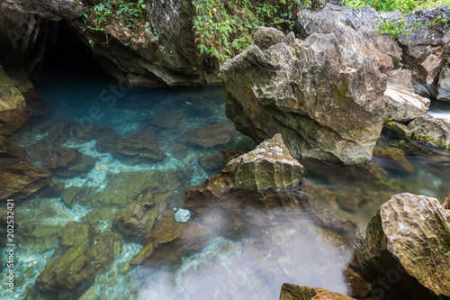 Foto op Plexiglas Japan Transparent and blue water at a rocky lagoon next to the Tham Chang (or Jang or Jung) Cave in Vang Vieng, Laos.
