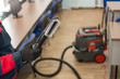 a professional cleaner man in uniform removes an office space with the help of an industrial vacuum cleaner. Cleaning services.