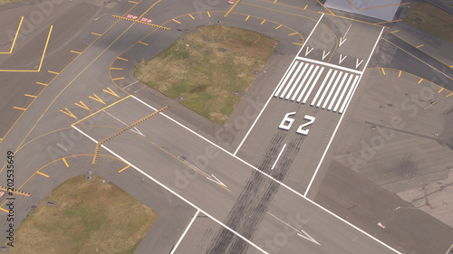 Fotografie, Obraz  AERIAL: Pavement surface and flight markings on empty runway field on airport