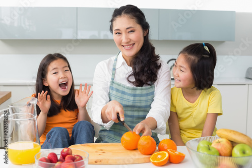 Valokuva  Woman with cheerful two daughters cutting fruit in kitchen
