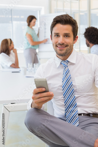 Fototapety, obrazy: Smiling businessman text messaging with colleagues at office