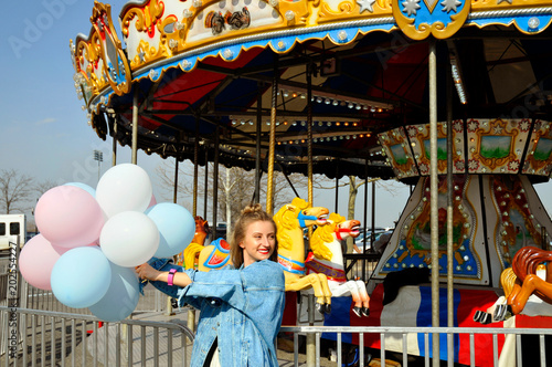 Foto  Beautiful young woman with balloons in the amusement park