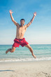 Happy man jumping on the beach