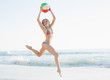 Gorgeous young woman jumping on beach holding a beach ball
