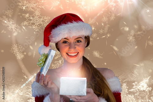 Sexy girl in santa costume opening a gift against cream snow flake pattern design