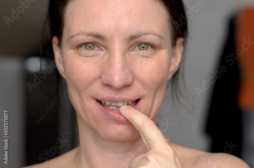 Attractive sensual woman with finger to her lips Poster