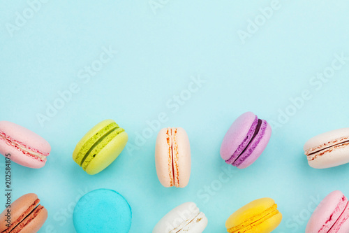 Photographie Macaron or macaroon on turquoise pastel background from above