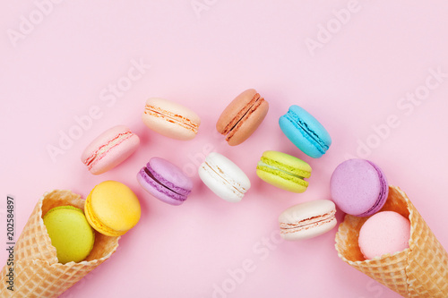 Foto auf Leinwand Macarons Waffle cone with cake macaron or macaroon on pink pastel background top view. Flat lay composition.