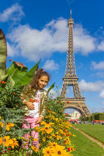 Foto  Girl on the field above Eiffel tower