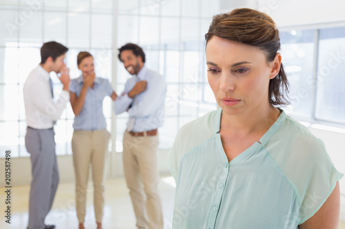 Fototapeta Colleauges gossiping with sad businesswoman in foreground obraz