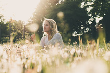 Daydreamer Woman Outdoor. Young Woman Sitting At Dandelion Field.