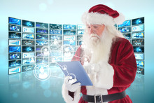 Santa Uses A Tablet PC Against Screen Collage Showing Business Images