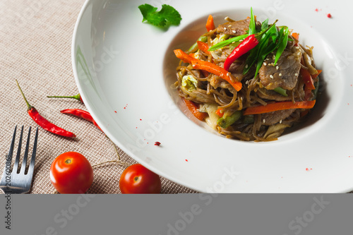 Deurstickers Klaar gerecht Healthy pasta with meat and vegetables on a white plate with with herbs and pepper