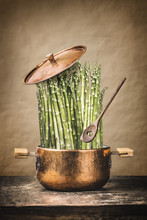 Asparagus In Cooking Pot With Wooden Spoon On Rustic Table , Front View.   Healthy Vegetarian Food And Eating Concept