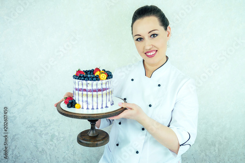 Beautiful And Smiling Woman Confectioner In White Work Uniform Adorns The Cake Kitchen Cooking Wedding Birthday With