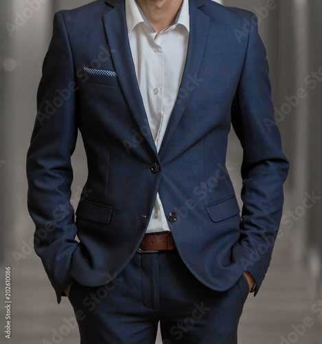 Cropped Head Man standing in a smart suit with hands in pockets in a passage Canvas Print