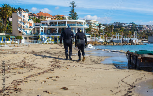 People in wetsuits walking on the seashore after the underwater search of coins with the metal detector Canvas Print