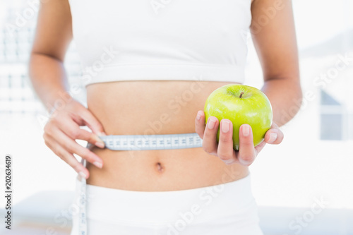 Láminas  Mid section of woman measuring waist as she holds apple