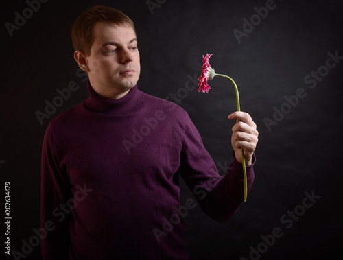 Fotografie, Obraz  Young man hold gerbera flower in hand. Selective focus.