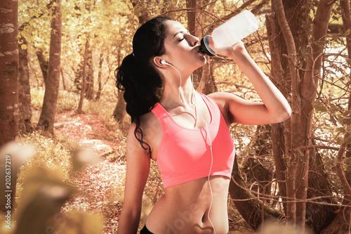 Papiers peints Orange eclat Beautiful healthy woman drinking water against peaceful autumn scene in forest