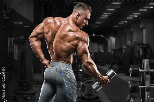 Fotografie, Obraz  Rear view muscular man showing back in gym
