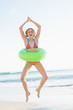 Joyful young woman holding a rubber ring jumping on the beach