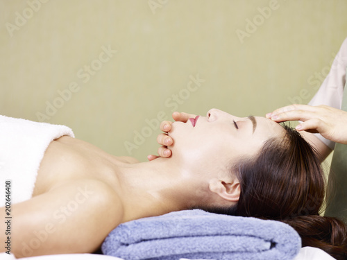 Photo  young asian woman receiving face massage in spa salon