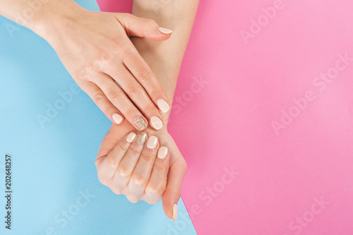 Foto op Plexiglas Spa Beauty girl hand with nails manicure on blue and pink background. Manicure and Hands beauty concept. Close up, top view