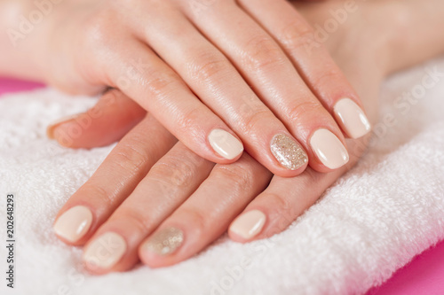 Photo sur Aluminium Manicure Young girls hands with cream color nails polish on fingers. Manicure and beauty hands concept. Close up, selective focus.