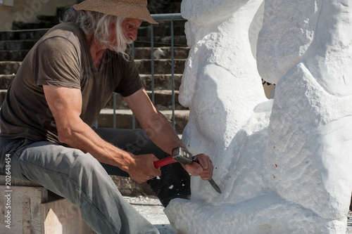 Canvas Print Sculptor at work on marble statue with hammer and chisel