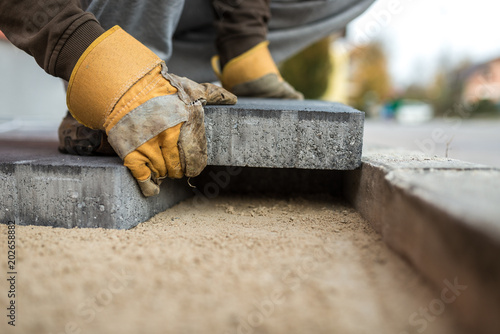 Photo Workman laying exterior paving stones